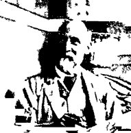 A low resolution black-and-white image of a bald man with a beard and kindly smile sitting at a desk with pen held in his right hand.