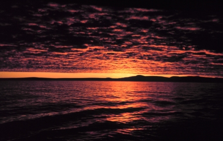 A sunset scene of an ocean with a distant coastline to the right. The blood-red and black colours of the sunset on the Bering Sea are analogous to the powerful tectonic forces and magma movements which created land in the midst of the Pacific Ocean, millions of years ago.