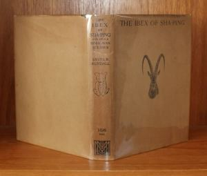 An opened book standing with its outer cover facing us. The dustjacket is on and is fawn coloured. The spine bears the names of the book and author, a caricature of a bear cub, the cost (ten shillings and sixpence) and the logo for McMillan who published the book. The front jacket has the name written along the top edge and the head of an ibex in the centre.
