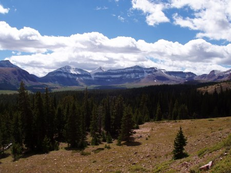 A pine-clad valley ringed with buttes and a snow-clad mountain, King's Peak above which white clouds cover most of a rich blue sky.
