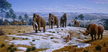 A herd of Wolly Mammoths cross the tundra watched by other animals - cave lions, horses and a woolly rhinoceros. Patches of snow cover the ground. In other places grass shows up. A few trees are also seen. The weather appears overcast with a few clouds. on the horizon.